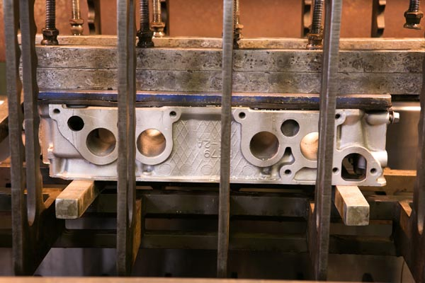 cylinder-head-in-pressure-testing-machine-side-view   Budget Engine Rebuilders